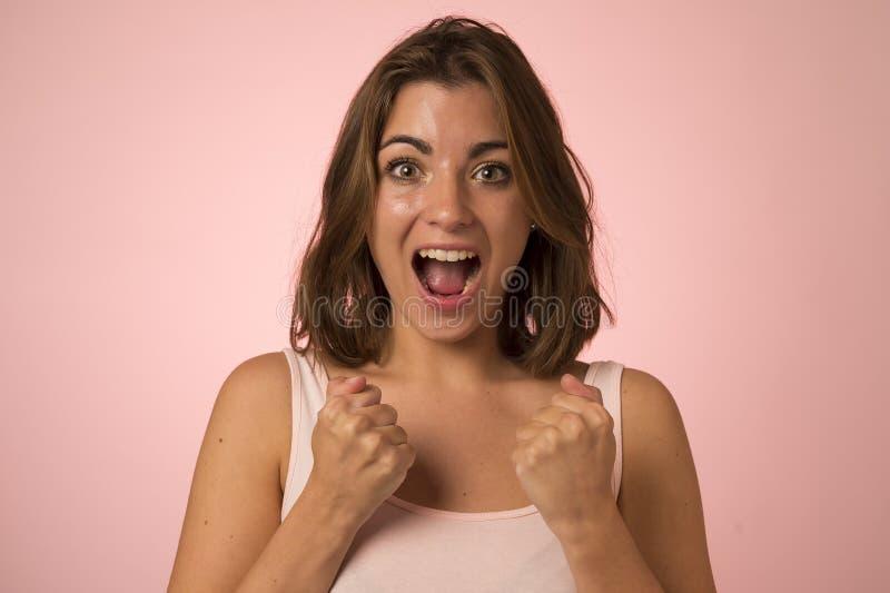 Ungt attraktivt och härligt le för kvinna som är upphetsat och som är lyckligt i vinnare och segergest royaltyfri fotografi