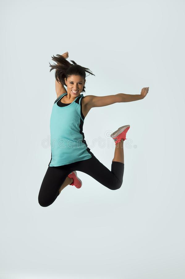 Ungt attraktivt och lyckligt latinskt hoppa för sportkvinna som är upphetsat och som är gladlynt i sund livsstil för idrottshallö arkivbilder
