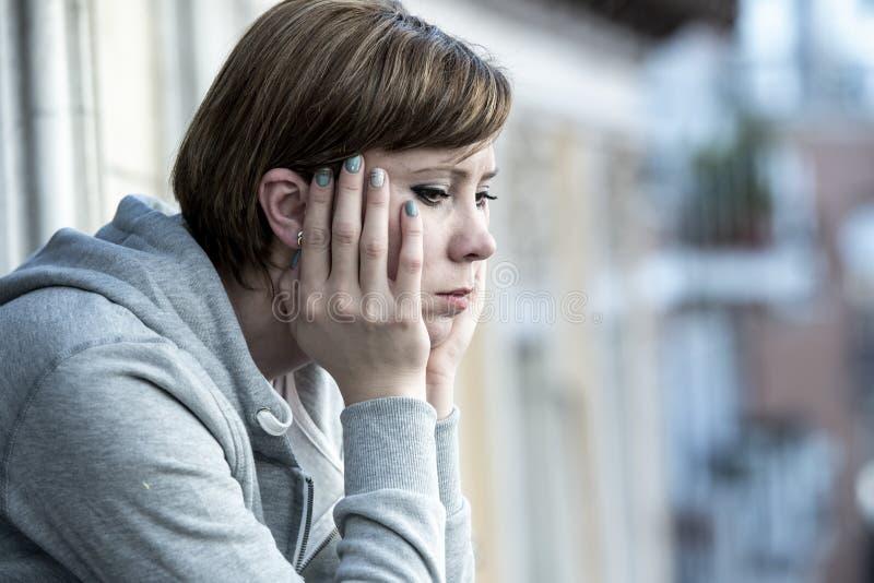 Ungt attraktivt olyckligt deprimerat ensamt stirra för kvinna som är hopplöst och som är bekymrat på balkongen hemma arkivfoton
