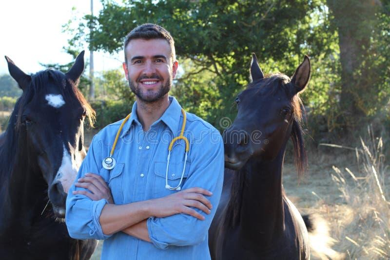 Ungt attraktivt veterinär- anseende bredvid hästar på ranchen med kopieringsutrymme royaltyfria bilder