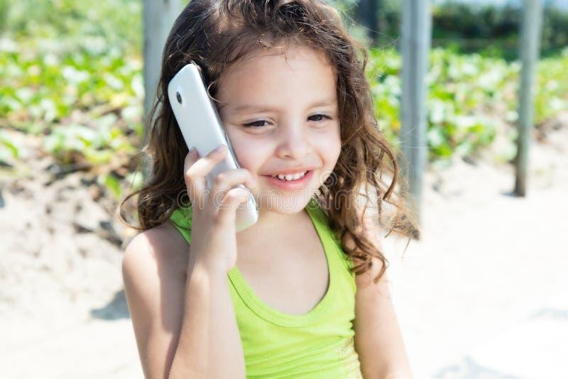 Ungt barn i en gul skjorta som skrattar på telefonen royaltyfri bild