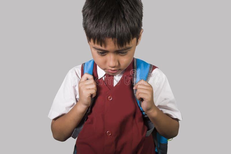 Ungt barn i skolalikformign som känner sig ledset och deprimerat se ner förskräckt och generat offer av pennalismen och missbruk arkivbild
