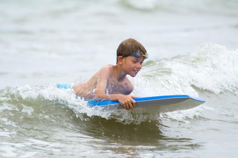 Ungt barn med en bodyboard på stranden royaltyfri foto