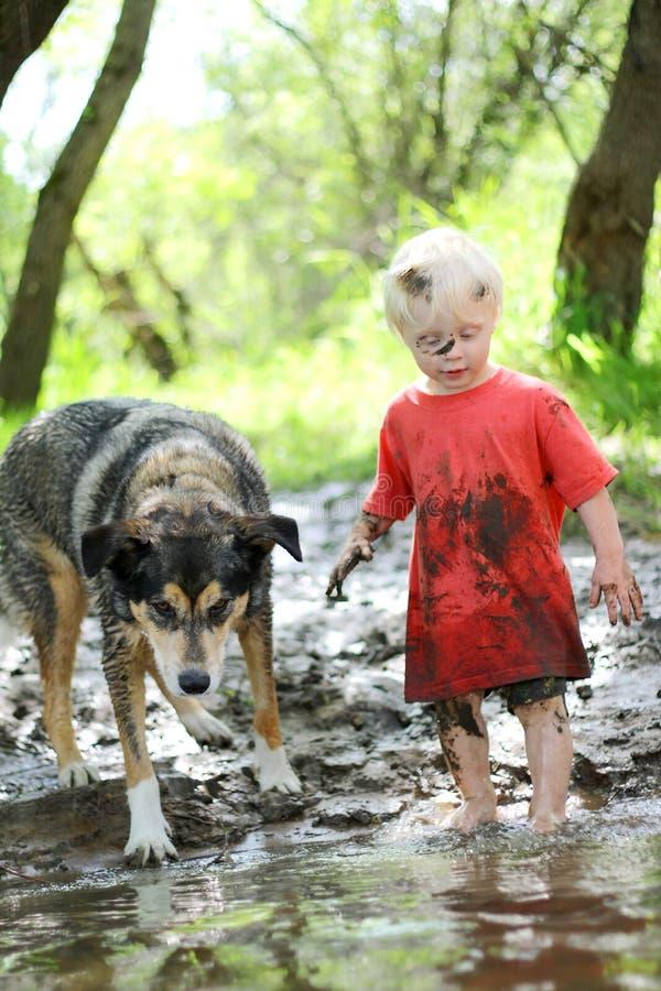 Ungt barn och hund som spelar i Muddy River royaltyfria foton
