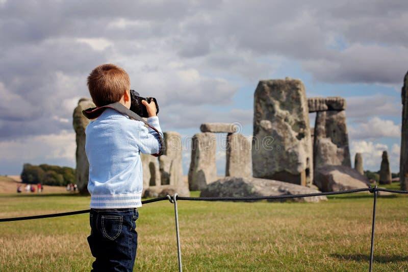Ungt barn pojke som tar pic med den digitala kameran på Stonehenge royaltyfria foton