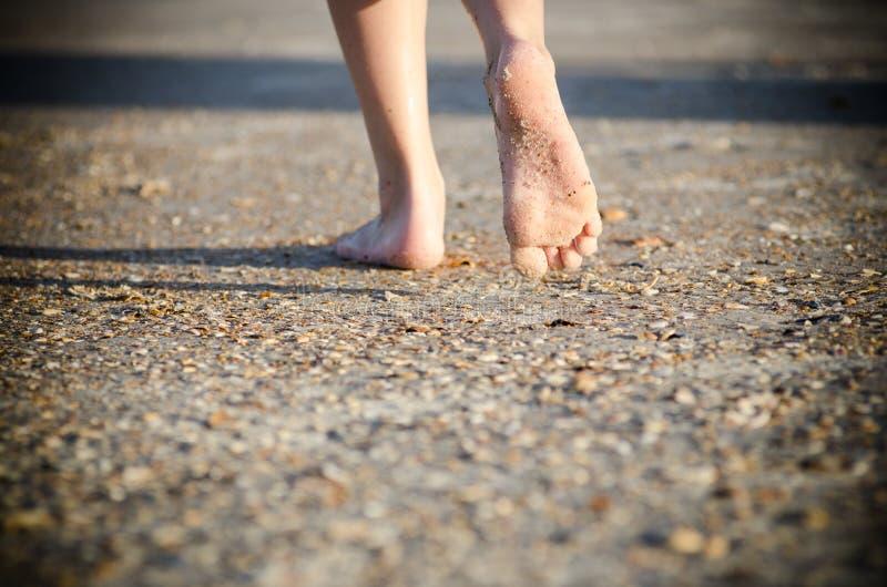 Ungt barn som barfota går på en strand fotografering för bildbyråer