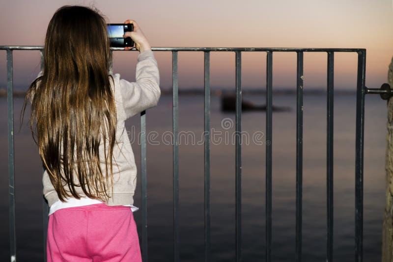 Ungt barn som tar bilden av havssikten arkivbild