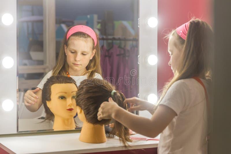 Ungt barnflicka som gör en hårstil som en frisör royaltyfri fotografi