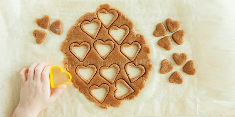 Ungt barnhänder förbereder degen, bakar kakor i köket Nära övre begrepp av familjleasuren arkivbilder
