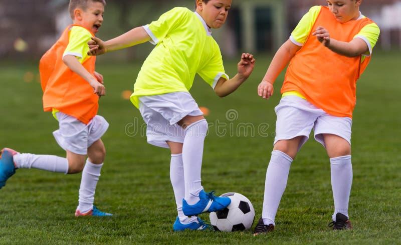 Ungt barnspelarefotbollsmatch på fotbollfält arkivbilder