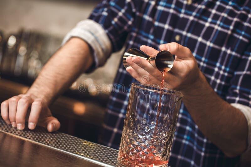 Ungt bartenderanseende på hällande whisky för stångräknare in i exponeringsglas fotografering för bildbyråer