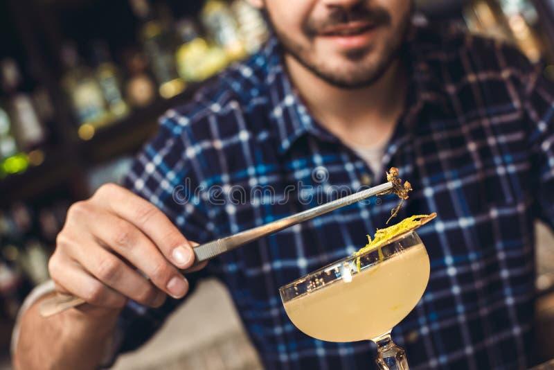 Ungt bartenderanseende på stångräknaren som dekorerar coctailen med örten som ler närbild arkivfoton