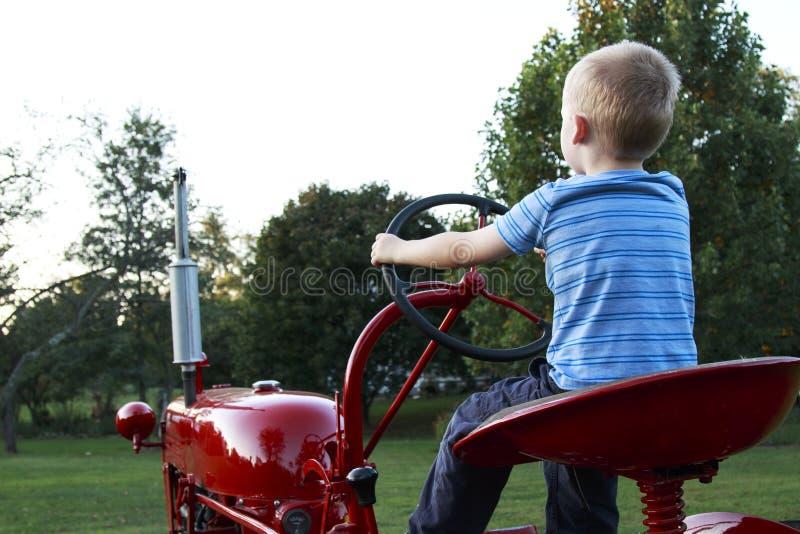 Ungt blont barn som låtsar för att köra en gammal röd traktor till royaltyfri fotografi