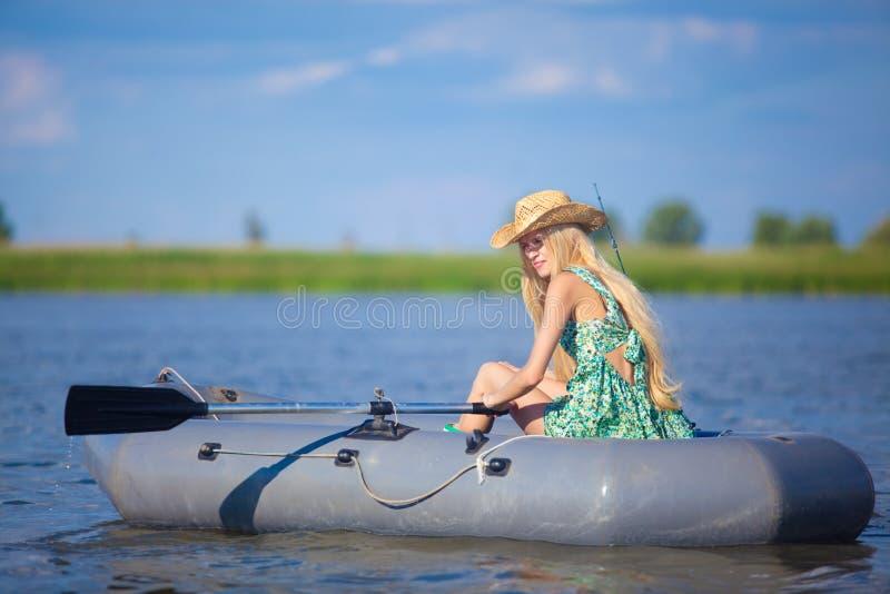Ungt blont flickafiske på fartyget i sjön royaltyfri foto