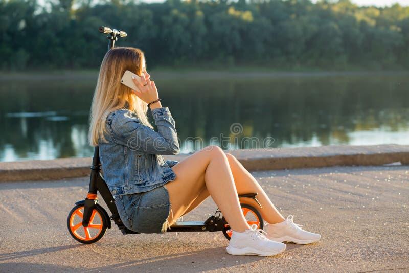Ungt blont kvinnasammanträde på en sparkcykel och samtal på telefonen i natur arkivfoton