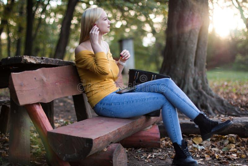 Ungt blont kvinnasammanträde på en träbänk i parkera och att lyssna till musik arkivbild