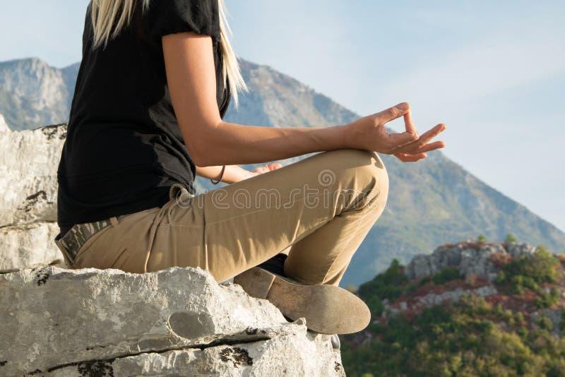 Ungt blont kvinnasammanträde på kanten av berget i klippa för yogameditationposition mot härligt bergmaximum fotografering för bildbyråer