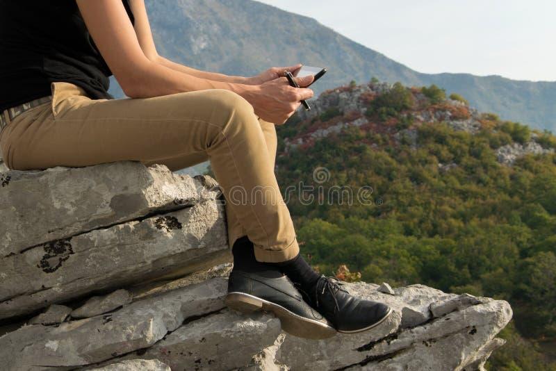 Ungt blont kvinnasammanträde på kanten av bergklippan genom att använda den digitala minnestavlan royaltyfri foto