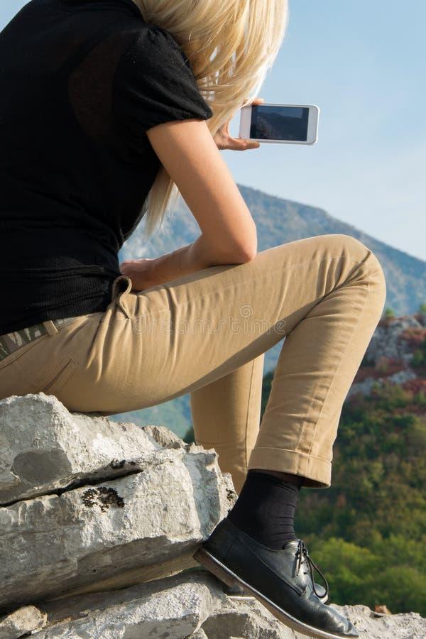 Ungt blont kvinnasammanträde på kanten av bergklippan tar fotoet med smartphonen på det härliga bergmaximumet royaltyfri bild