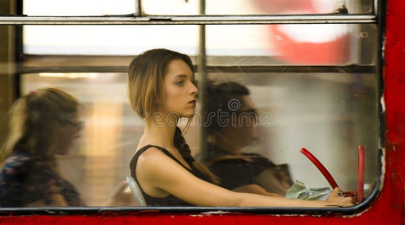 Ungt blont tonårs- kvinnasammanträde, medan rida i en fönsterplats royaltyfri foto