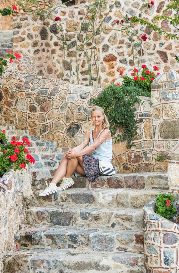 Ungt blont turist- kvinnasammanträde på forntida stentrappa i den gamla staden, Alanya, Turkiet royaltyfria bilder