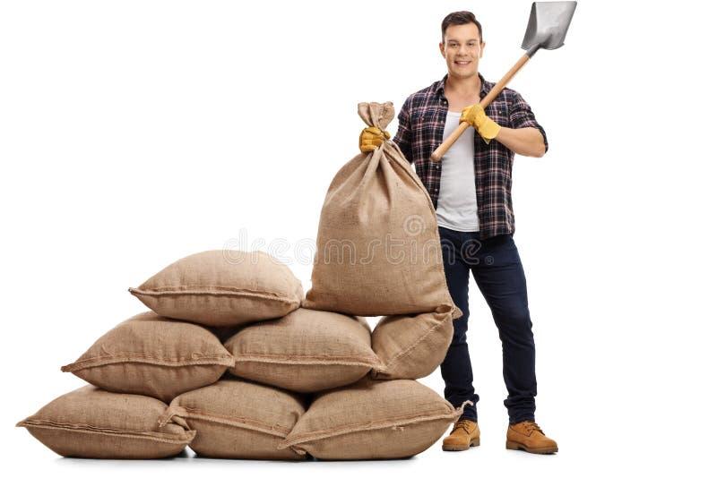 Ungt bondeanseende bredvid högen av säckvävsäckar och innehav s royaltyfria foton