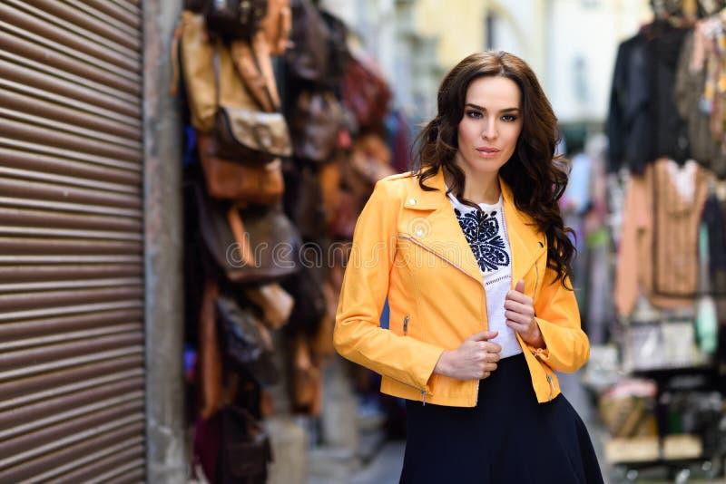 Ungt brunettkvinnaanseende i stads- bakgrund arkivfoto