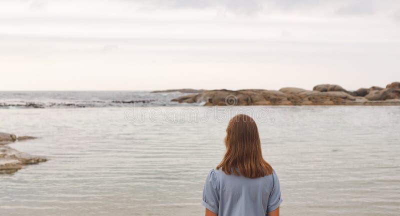 Ungt Caucasian kvinnaanseende på stranden royaltyfria foton