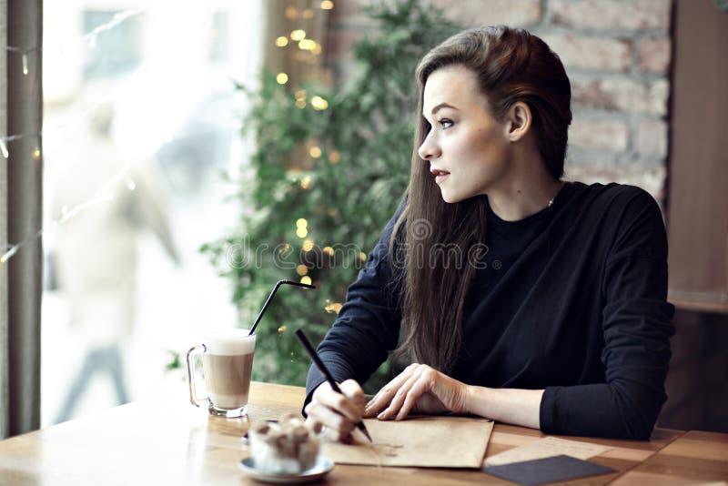 Ungt caucasian kvinnaarbete, handstil i en restaurang äganderätt för home tangent för affärsidé som guld- ner skyen till Stationä arkivfoto