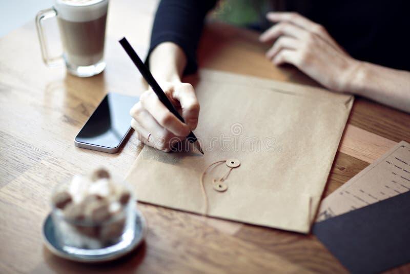 Ungt caucasian kvinnaarbete, handstil i en restaurang äganderätt för home tangent för affärsidé som guld- ner skyen till Stationä arkivfoton