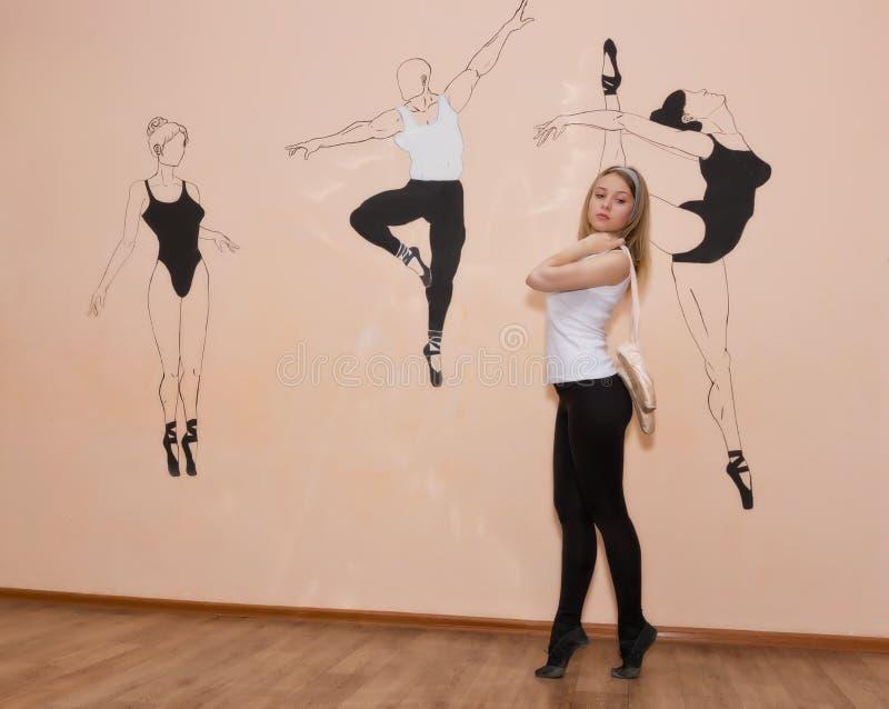 Ungt dansareanseende på hennes tår i en balettslagställning med Pointe fotografering för bildbyråer