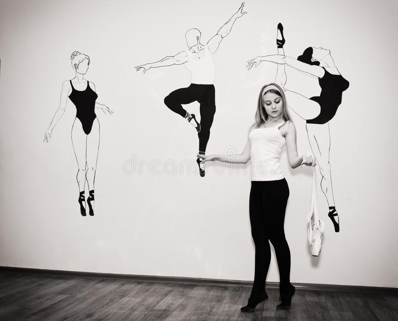 Ungt dansareanseende på hennes tår i en balettslagställning med Pointe royaltyfri foto