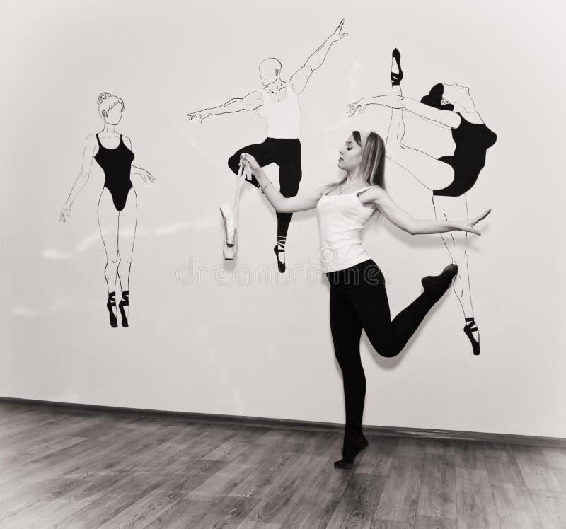 Ungt dansareanseende på hennes tår i en balettslagställning med Pointe royaltyfri fotografi