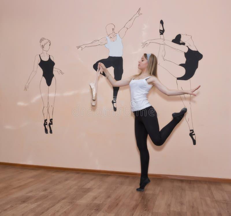 Ungt dansareanseende på hennes tår i en balettslagställning med Pointe arkivbild