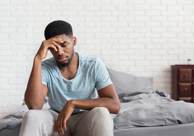 Ungt deprimerat svart mansammanträde på säng royaltyfria bilder