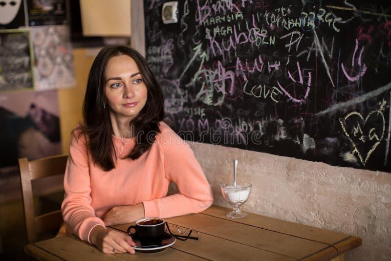 Ungt drömlikt flickasammanträde i ett kafé relax royaltyfria bilder