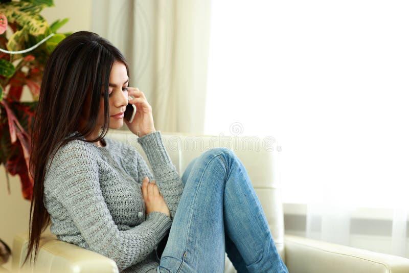 Ungt eftertänksamt kvinnasammanträde på soffan och samtal på telefonen royaltyfri fotografi