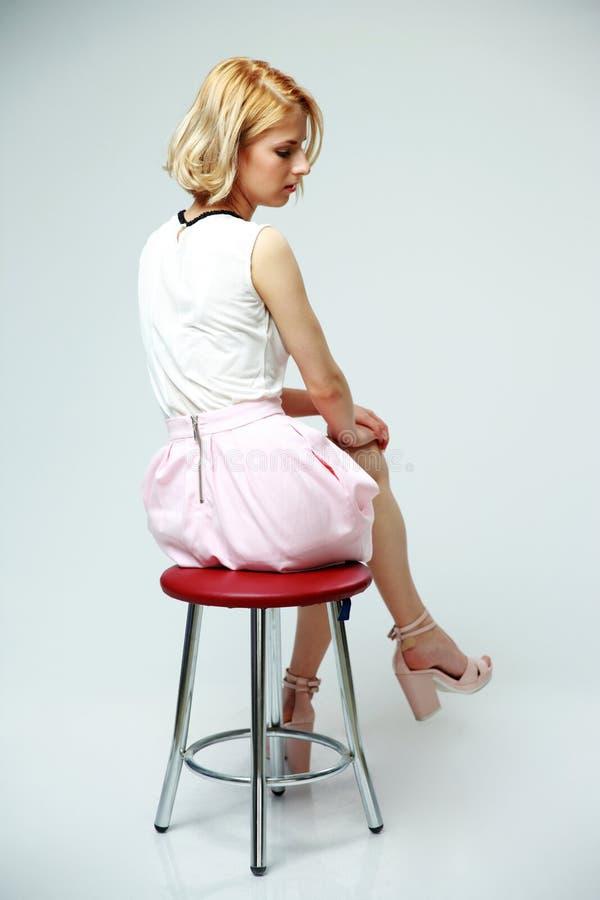 Ungt eftertänksamt kvinnasammanträde på stolen arkivfoto