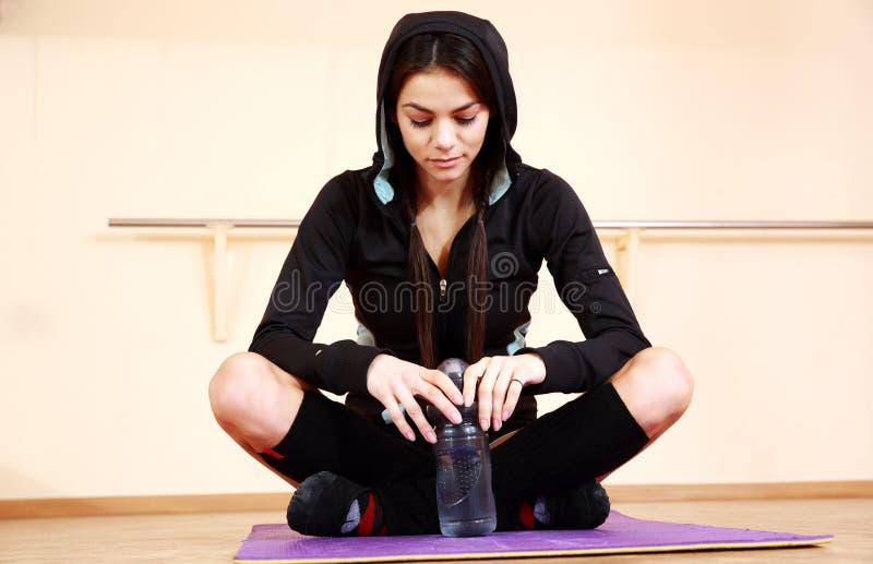 Ungt eftertänksamt passformkvinnasammanträde på den matta yogan royaltyfria foton