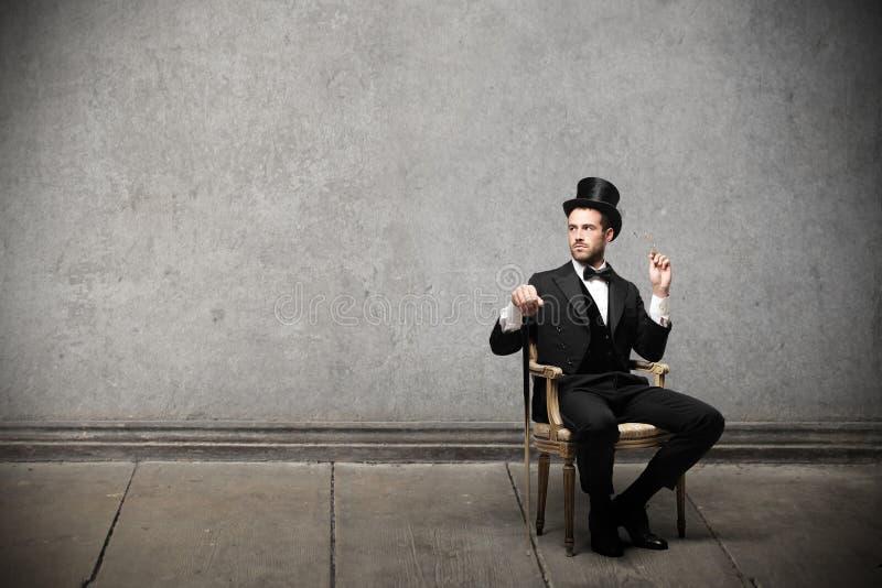 Ungt elegant mansammanträde på en stol royaltyfria foton