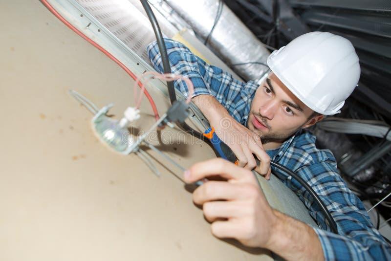 Ungt elektrikerfixandeneon på tak royaltyfri foto