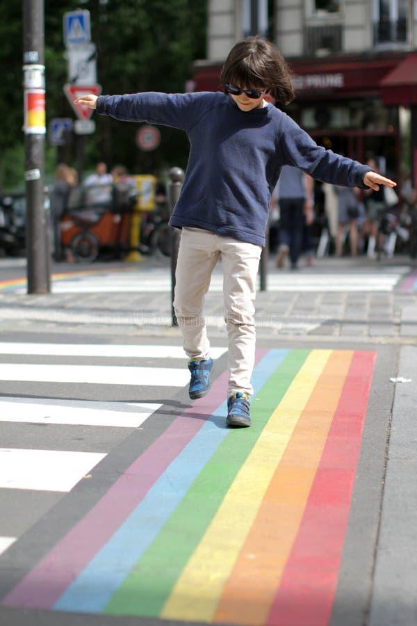 Ungt försiktigt barn som korsar gatan med gyckel, stadsbakgrund arkivfoton