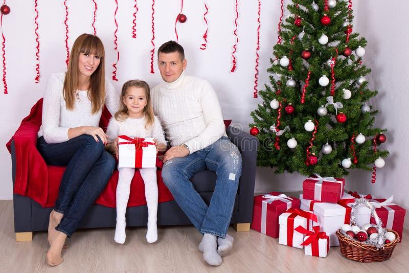 Ungt familjsammanträde i dekorerad vardagsrum med jultre arkivfoton