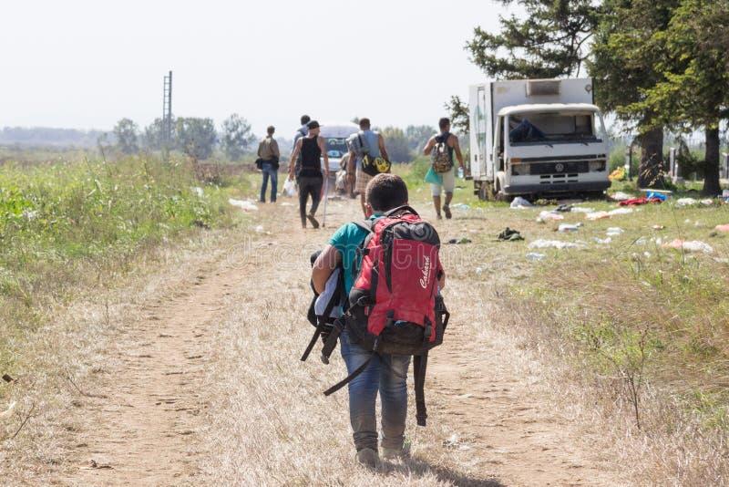 Ungt flyktingbarn som bär den tunga ryggsäcken på den KroatienSerbien gränsen, mellan städer av Sid & Tovarnik på den Balkans rut royaltyfri fotografi