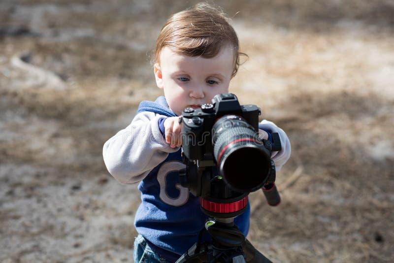 Ungt fotografbarn som tar foto med kameran på en tripod arkivfoton