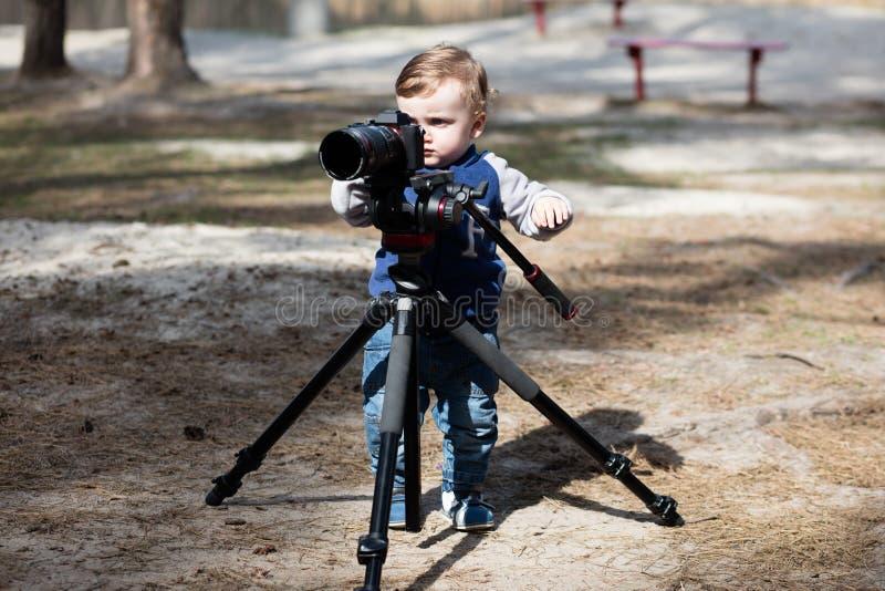 Ungt fotografbarn som tar foto med kameran på en tripod fotografering för bildbyråer