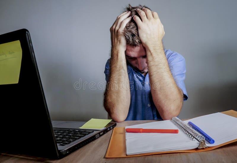 Ungt galet stressat och förkrossat arbeta för man som är smutsigt på kontorsskrivbordet som är desperat med framsidan för beläggn royaltyfri bild