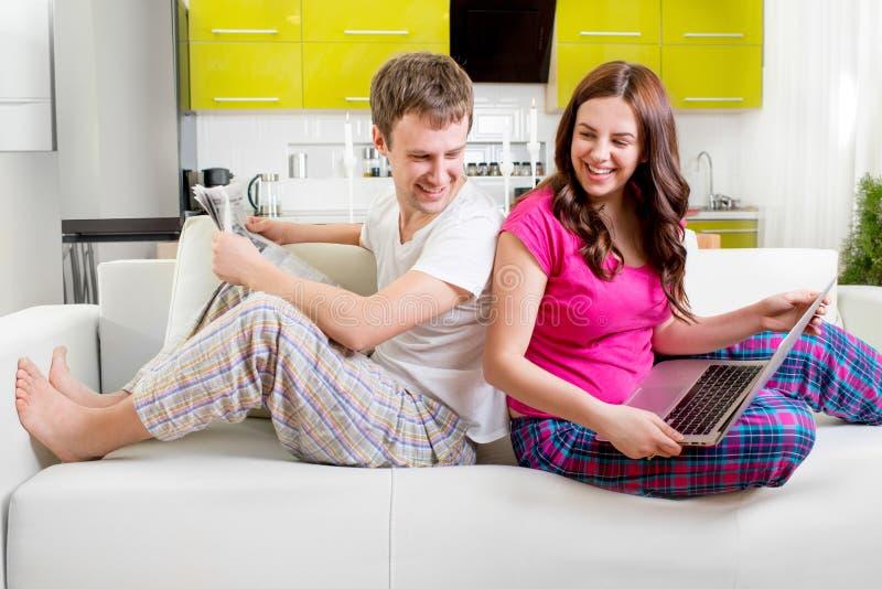 Ungt gift par i pyjamas som sitter i den läs- nyheterna för soffa royaltyfri foto