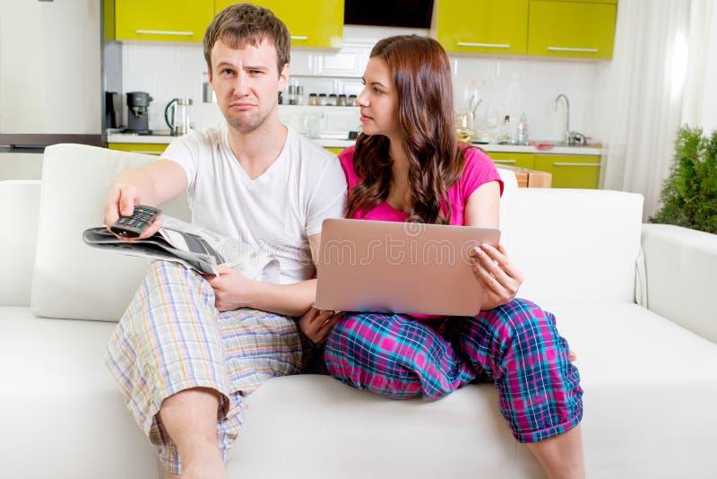 Ungt gift par i pyjamas som sitter i soffan med newspap royaltyfri foto