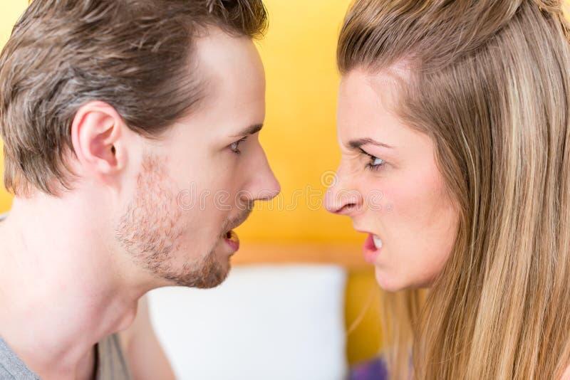 Ungt gift par, kvinna och man, i rasande stirra för kamp royaltyfria bilder